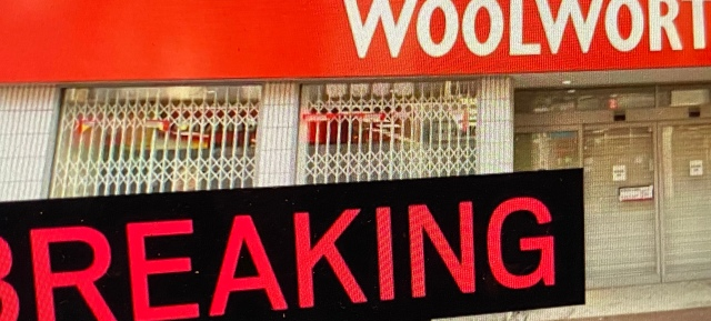 Breaking news logo in front of a Woolworths high street store